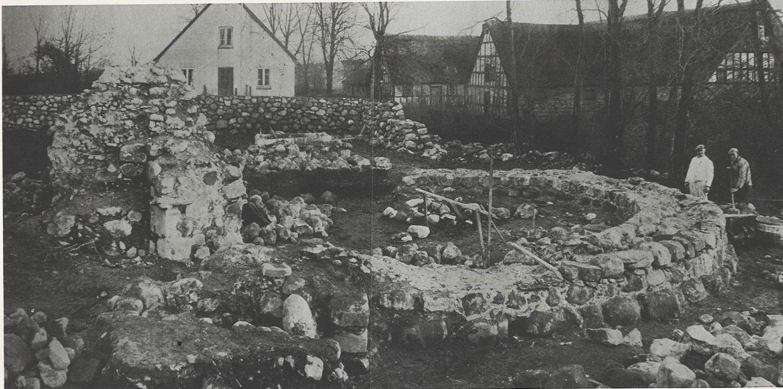 Ruinen ved Malling Kirkegård. Kampestensmurer Jens Andersen, Fløjstrup. Manden til højre er Niels Christensen, Fløjstrup. I baggrunden Lundshøjgårdvej. Stuehuset til præstegården nedrevet i 1959. Foto ca. 1938