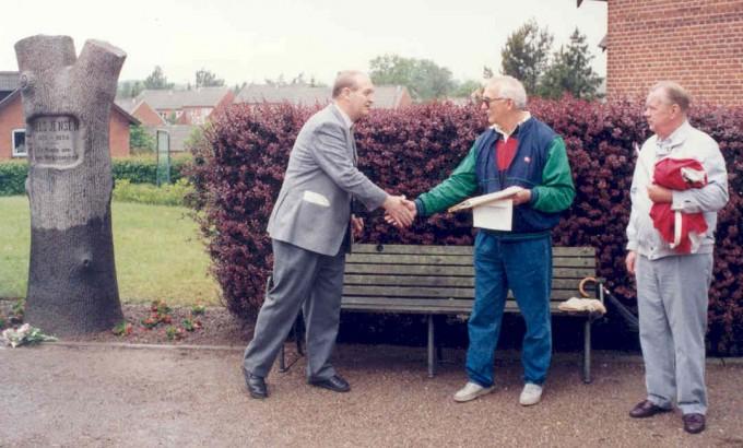 På et tidspunkt i 1960'erne fylder mindestenen for meget på Stationspladsen, og den fl yttes op i haven ved Beder-Malling Boligforening. Her er den ikke særlig synlig, og i 1991 fl yttes den igen til den nuværende placering. På billedet fra indvielsen i 1991 ses arkivleder Anders Nørgård (midtfor), formand for lokalhistorisk forening Anders Nielsen, tv., og en slægtning til Niels Jensen, Gudmund Jensen.