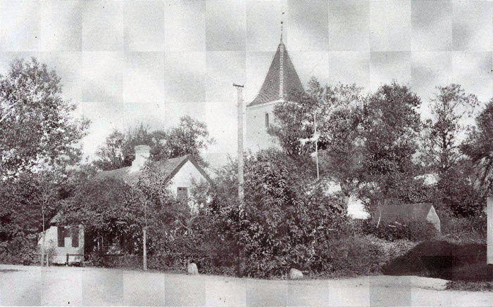 """Malling Kirke omkring 1890. I det hvide hus til venstre boede Ann og Søren Nielsen. Det lille kampestenshus er sprøjtehuset, altså byens """"brandstation"""", hvor den håndbetjente sprøjte havde sin plads. Bagved kan man se noget hvidt. Det er ringerhuset, hvor ringeren og graveren boede. Yderst til højre skimtes lidt af udbygningerne til """"Stenhøjgård"""", der omkring 1900 blev flyttet øst for byen, nu børnehaven """"Stenhøjgård"""". Se andet billede i kalenderen."""