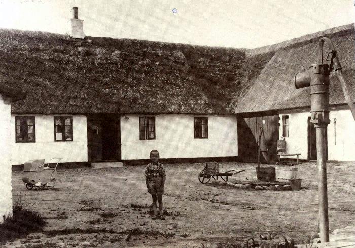 Et dejligt gårdmiljø omkring 1940 fra Synnedrupvej 40. Midt på gårdspladsen står Svend Madsen, søn af gårdens ejere Hertha og Tage Madsen. På gårdspladsen ses en flot barnevogn, en fladbør, en vandpumpe med vandtrug foran, hvor heste og kreaturer blev vandet, samt i forgrunden til højre ajlepumpen, hvormed man pumpede ajlen, den tids gylle, op fra ajlebeholderen.