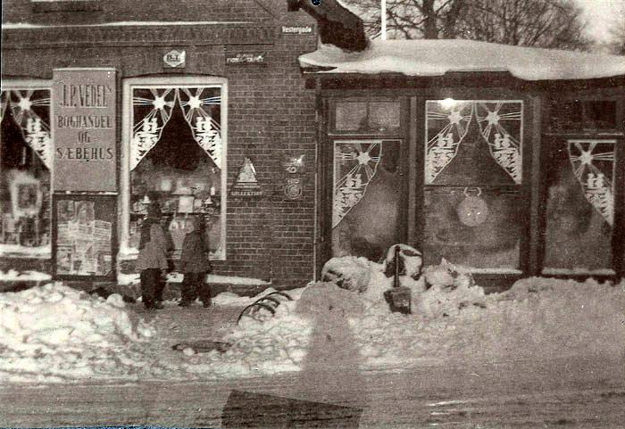 Ingrid Vedels boghandel Gl. Østergårdsvej 16, Malling. Julen er nær, og Ingrid Vedel har julepyntet sine vinduer med kunstfærdigt juleklip. Foruden bøger blev der solgt papir, og som man kan se på skiltet, sæbe. Ingrid Vedel var meget glad for hunde, og hvis man havde sin lille hund med, blev den først klappet og kælet for i lang tid, og så kunne man få det, man ønskede. Børnene, der ser ind af vinduet, er Lisbeth og Kirsten Frandsen.