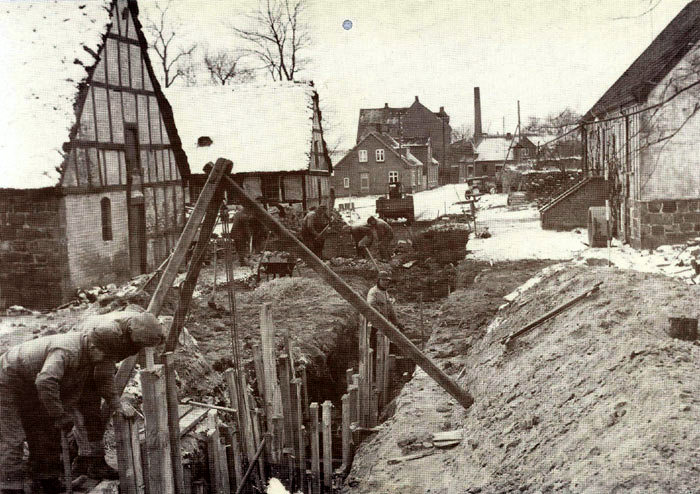 """Opgravning af kloak til Malling skole, der blev taget i brug august 1959. Billedet her er fra d. 14. dec. 1957, og med den seneste kloakering i erindring må dette kaldes primitivt, men det fungerede. Gennembrydningen foregår ved """"Lundshøj gård"""", hvor stuehuset til højre nu er præstebolig, mens der er P-plads. hvor udbygningeme lå. Vejen er nu forbindelsesvej mellem Kirkevej og Lundshøjgârdsvej. Personerne kendes ikke. Måske kan du hjælpe os?"""