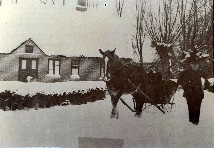 """Postbud Vilhelm Pedersen. også kaldet 'Bødkerposten"""", på posttur i Fulden sidst i 1930erne. Det var almindeligt at """"posten"""" cyklede eller gik rundt til alle huse på en lang rute, måske omkring 20 km. Det var en meget hård tur om vinteren, når sneen lå højt. Men undertiden stillede en landmand en hestekane med kusk til rådighed. Kanen her har Svend Pedersen, Beder stillet til rådighed for posten. Kusken er ukendt. Huset i baggrunden tilhørte Petrea Nicolaisen, i 1940 flyttede Magnus og Valborg Christensen ind i huset. Kunstmaleren Voldby og Per Fulling har tidligere boet i huset."""
