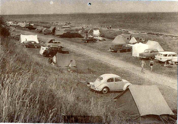 Ajstrup Strand juli 1962. da det endnu var tilladt at campere på stranden og pigerne endnu ikke var topløse. Som man kan se. blev den flittigt brugt, og Beder-Malling Kommune havde du også opført toiletter og vaskepladser til campisterne. Toiletterne findes stadig. Bemærk bilerne, som alle er europæiske. De japanske var endnu ikke indført.