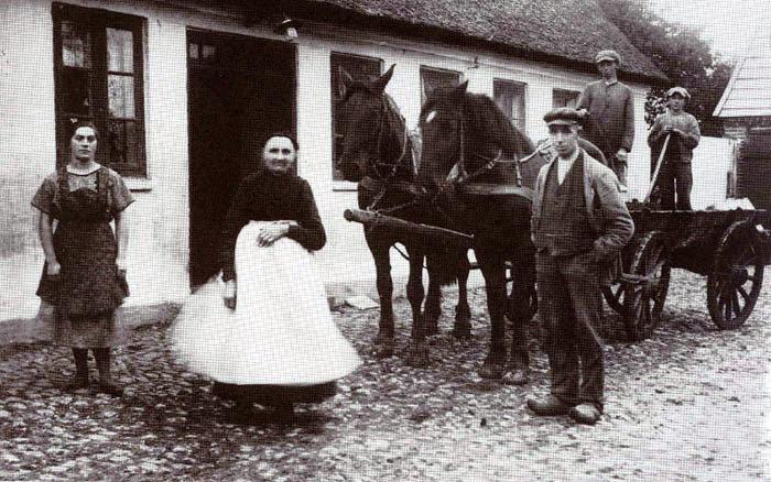 """Vestergaard"""", Lillenor, ca. 1928: Gården er en gammel slægtsgård og har, før den blev frikøbt, været fæstegård under Aarhus Hospital. På billedet ses gårdejer Karl Sørensen sammen med sin mor (med hvidt forklæde) og tjenestepige og -karle. Navnene kendes ikke."""