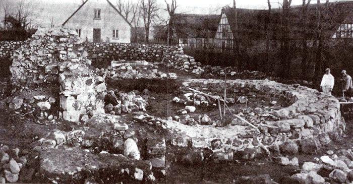 """Fæstningsruinen ved Malling Kirke, da den blev restaureret i 1943 - 44. Fæstningen, der anslås at være anlagt i 1200 - tallet, er et fortidsminde af ganske særlig karakter. På billedet ses kampestensmurer Jens Andersen, Fløjstrup, og en medhjælper i færd med at genopbygge ruinen. I baggrunden """"Lundshøjgaard"""", hvis udhuse blev nedrevet i 1959, medens stuehuset til venstre nu er præstebolig."""