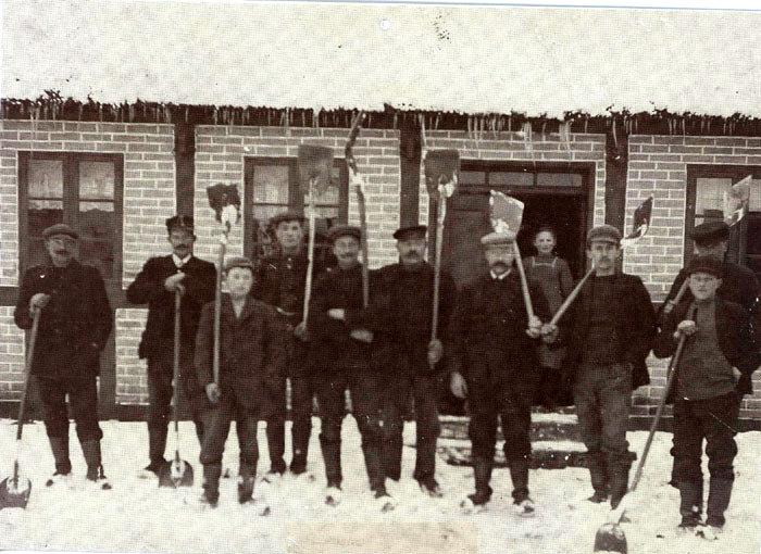 Malling Bjergevej 119 omkring 1920, hvor Bolette Øvlisen står i dæren, og broderen Niels står som nr. 4 fra venstre. Manden med skæg foran Bolette er Ole Olesen, der var ladefoged på Norslund. De to første fra venstre er henholdsvis forkarl og kusk på Norslund. Navnene kendes ikke, og heller ikke på de øvrige. Når der skulle ryddes sne, skulle hver gård stille en eller flere karle efter gårdens størrelse. Snekastningsholdet blev ofte inviteret på kaffe, og tit blev skovlene så varmet på komfuret, og derefter smurt med talg, så sneen bedre kunne slippe.
