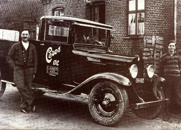 Ceres depotet, Malling. Billedet stammer fra 1929, hvor den nye Chevrolet lastvogn var komme! til Malling. Depolets indehaver Thomas Schou står til venstre, sønnen Svend Schou til højre og inde i bilen sønnen Hans Schou, der senere blev ejer af depotet. Bilen kostede 7000 kr. Man havde haft biler tidligere, men denne var noget særligt, da den var 6 cylindret. Bygningen bagved er depotets beboelse, nu GI. Østergaardsvej 1.