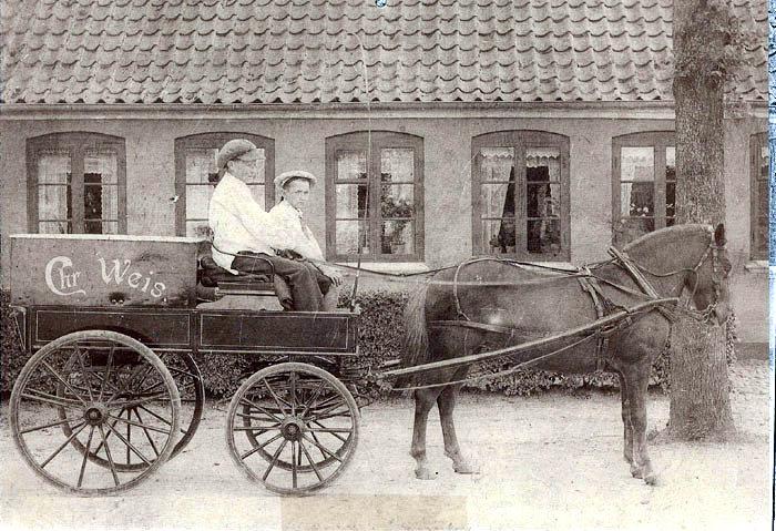 Beder Landevej omkring 1910. Slagtenmester Christian Weiss hestevogn, hvor sønnerne Jørgen og Johannes sidder på bukken. Vognen kørte rundt på landet med kød, som man havde i kassen bagpå. Et par låger bag på kassen kunne lukkes op, og bagklappen pá vognen slås ud, så den kunne fungere som disk og skærebræt. Kunden kunne så vælge sit kød, hvorefter det blev vejet pá bismervægten. Slagter Weis havde forretning i nr. 49, men vi mener, at vognen holder foran nr; 48, hvor nu Kirsten og Søren P. Pedersen bor.
