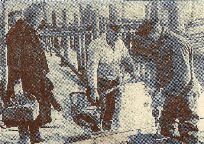 Katrine Nielsen, kaldet ÅIe-Katrine henter fisk ved havnen i Norsminde. De to fiskere er Sigfred Pedersen og Peter Pagh Pedersen. Bagefter gik Katrine rundt til sine kunder med skrubber og torsk, som hun hurtigt fik solgt, da man vidste, at de var helt friske. Turen var på ca. 10 km. Katrine boede i en jernbanevogn i Neder Fløjstrup. Vognen var købt af H. H. J. i 1936 for 200 kr. Den er nu ved at blive restaureret i Bindeballe og skal på privatbanemuseum. Billedet er fra omkr. 1950.