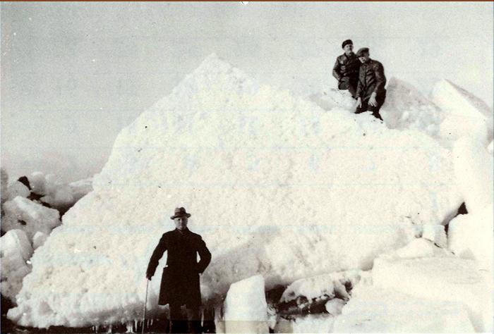 Iskolosser på stranden ved Norsminde i 1943. Gennem 3 år var det hver vinter særdeles hårde frostgrader, på visse steder omkring 30 graders frost. Sunde og bælter var tilfrosne, så man bl. a. kunne gå over Storebælt. Også Århus Bugt var tilfrosset, og når der så kom en kraftig storm, blev de store isblokke presset op på stranden. Højden af denne blok kan man fornemme ved at sammenligne med de 3 personer på billedet. Forrest sognefoged Niels Peter Nielsen og på blokken bestyrer på De gamles Hjem Åge Viktor: og antikvitetshandler Niels Schou, Malling.