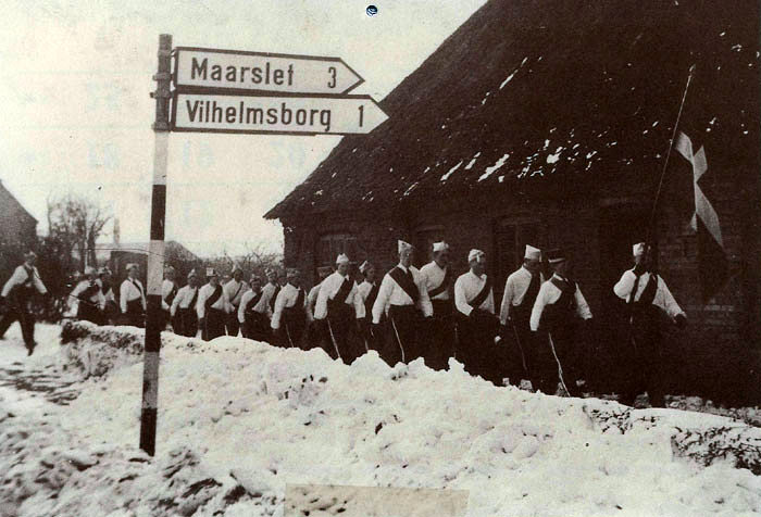 """Fastelavnssoldater på. Landevejen i Beder ca. 1951. Også i Ajstrup og Malling gik drengene fra de ældste Masser rundt og sang og indsamlede penge til en fest, som foregik på skolen eller i forsamlingshuset. Ældste dreng i 7. kl. var konge og holdt styr på pengene. Som man kan se var alle i en """"uniform"""" dvs. en hvid skjorte, skærf, bukser med påsyede hvide galoner samt skråhue. På billedet ses forfra: Svend R. Pedersen. Sven Gisselmann, ?, ?, Polle Pedersen, Svend Arne Bønnerup. Bagerst Kurt Lauversen."""