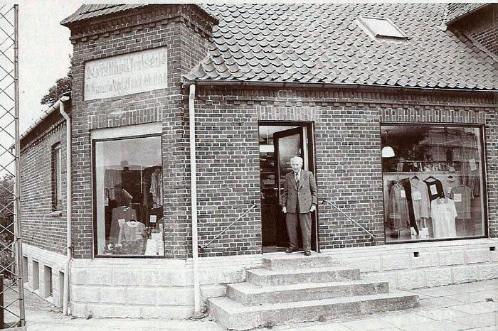 """Billedet er taget d. 20. oktober 1999, men rummer en masse historie. Denne dag åbnede Vilhelm Gammelby Jensen igen den butik, som han havde drevet fra 1936 til 1975. Forretningen købte han af sin far Kristian Jensen, som havde ladet ejendommen opføre i 1887. I 1938 startede Vilhelm Gammelby Jensen forretningen """"Rask handel"""" i Århus. I december 1999 blev Vilhelm Gammelby Jensen 94 år."""