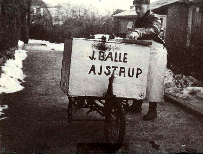 Fiskemand Jens Balle, Ajstrup, på Nyvej 1 Malling omkr. 1960. Jens Balle var først murerarbejdsmand, men i 1946 begyndte han at køre rundt som fiskehandler. Fiskene hentede han i Norsminde på sin budcykel, så kørte han rundt på egnen og solgte dem. I de første år havde han fiskene i tiskekasser, men kravene fra myndighederne blev større og større, og da man så i 1968 krævede, at han skulle have en håndvask, så opgav han. Det var ikke en formildende omstændighed, at hans tisk altid var sprællevende.