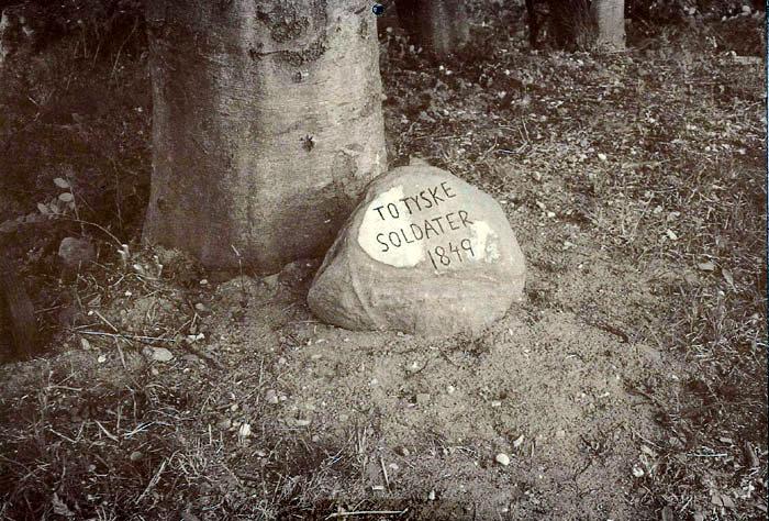 Mindesten over 2 tyske soldater. som faldt her i 1849. Danmark r i krig med Tyskland. og Jylland var bosat af tyske soldater op til Århus. Tyskerne havde dannet en vagtkæde fra Fulden til havet. men en dragon fra Randers dræbte de 2 soldater. Ca. 100 år senere mente pastor emeritus Rasmus Baden, Højbjerg, at de burde mindes, og han huggede stenen og anbragte den her på hjørnet af Bispelundvej og Kvægdriften, hvor man mener, at de faldt.