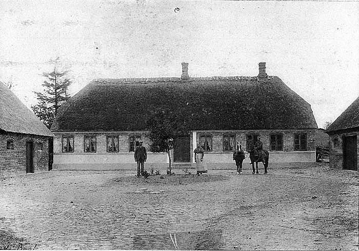 """Et dejligt gårdparti fra omkring 1910. Gården er """"Sørensminde"""" i Pedholt. Personerne er Paul Nielsen og Karen Marie. mens deres søn Thomas sidder på hesten klar til at spænde for. Thomas Nielsen overtog gården i 1914. Nuværende ejere af gården er Birthe og Bent Vange Nielsen."""