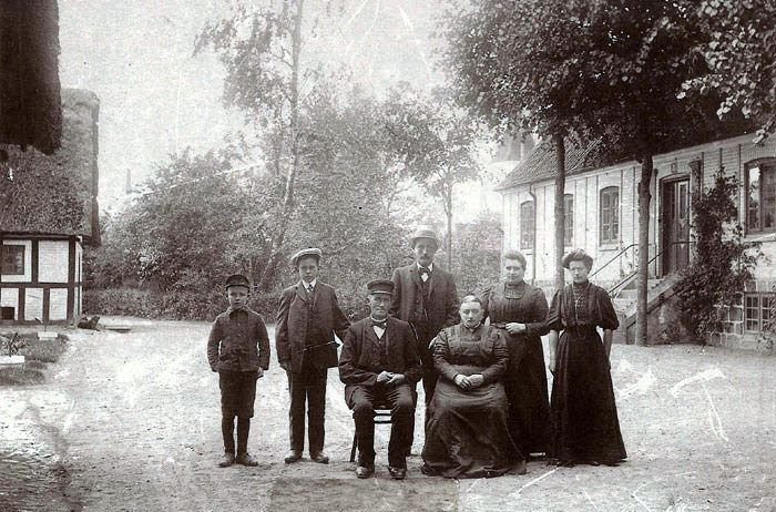 """Billedet er fotograferet på """"Lundshojgaard""""'(nu præstebolig) omkring 1905. Fotografen er Eisenhardt fra Odder, som tog ud og fotograferede rundt omkring. Så iførte man sig det fineste tøj, og alle på gården skulle med på billedet. Laurs Jakobsen står i midten bagerst og ved siden af ham hans kone Birthe Marie samt hendes søster. Sandsynligvis er parret foran Birthe Maries forældre, som de overtog gården efter i 1894. Laurs og Birthe Marie skænkede L920 """"Egelund"""" til Malling Håndværker og Borgerforening. Se stenen ved indgangen til hallen."""