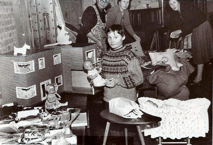 Basar på Beder Skole i 1961. Forrest står Hanne Clausen med en dukke. Bagved ses fra venstre Tyra Clausen, Esther Gisselmann og Kirsten Klougart.