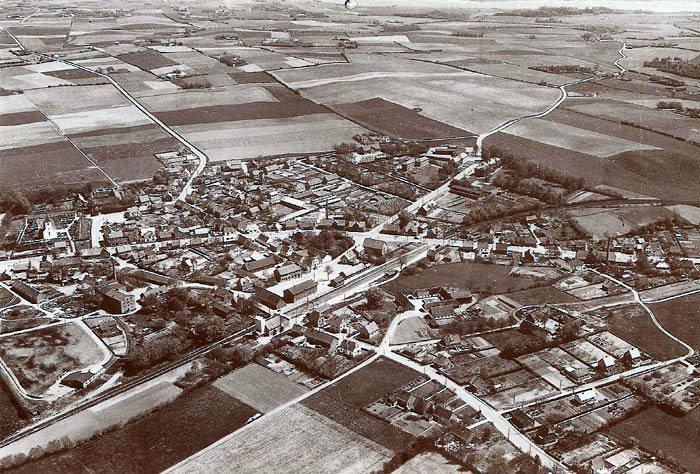 Et luftfoto fra Malling By, set fra vest. Året er 1956, altså før den store udbygning begyndte. I venstre side af billedet ses kirken, Lundshøjgaard og Malling Dampmølle. I midten ses Aaby Madsens Savværk og Stavfabrik, på hvis grund Super Brugsen nu ligger. Til højre ses Toftegaarden og Smedegaarden.
