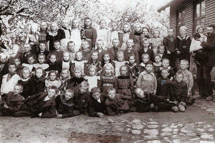 Ingen på Egnsarkivet forventer, at nogen husker personerne på dette billede fra Ajstrup Skole i 1902. Børnene er i deres stiveste puds i anledning af fotograferingen, som på det tidspunkt ikke var en dagligdags foreteelse. De ældste drenge i jakkesæt (konfirmationstøj), de lidt yngre i matrostøj. Pigerne kan man næsten inddele familievis, idet deres kjoler er syet af det samme stof, eller deres kraver er ens hæklede. De havde hvide forklæder på for at skåne tøjet. Eneste kendte elev er drengen i øverste række t.h. i sømandsuniform. Han hedder Hilding Olsen og var plejebarn hos fisker Jens Nielsen i Norsminde.