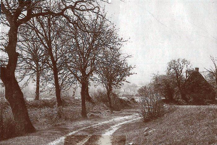 """En vinterdag ved """"Samshuset"""". - Huset lå på den lille vej, der går fra Fulden til Moesgaard Allé og som i daglig tale blev kaldt for """"Samsvejen"""". Huset hørte til Moesgaard og beboedes af familier, der havde deres arbejde der. Huset er nu væk."""