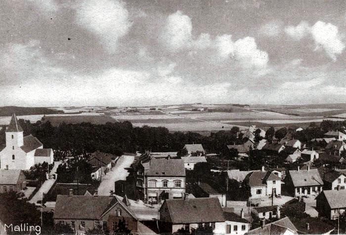 Østlige del af Malling i 1920'erne. Det er et interessant billede med mange spændende detaljer. Ved Malling Kirkevej ses t.v. nogle lagerbygninger, som hørte til købmandsforretningen på hjørnet (Danske Bank). For enden af vejen mellem træerne ligger Lundshøjgård, stuehuset er nu præstebolig. Nederst t.v. ses Gammelby Jensens forretning, og på modsatte hjørne af Gl. Østergårdsvej ligger skræddermester Georg Kristensens hus, det blev revet ned i 1959. Prøv selv at se nøje på billedet, og vil du vide mere om det, kan du besøge Egnsarkivet.