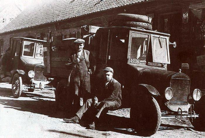 Et skønt gammelt billede fra først i 1920eme. 2 flotte lastbiler holder udenfor købmanden i Beder. De stolte chauffører får sig et lille hvil. Der er flere spændende detaljer på de 2 køretøjer. F.eks. håndsvingene. Den tids biler havde ikke selvstarter, så motoren skulle startes med håndsving. Med et håndtag under rattet kunne tændingen ændres, så motoren ikke slog tilbage. Foran var der en ståltråd med øje. Når man trak i den, fik motoren ekstra benzin til starten. Efter starten ændredes tændingen til normal.