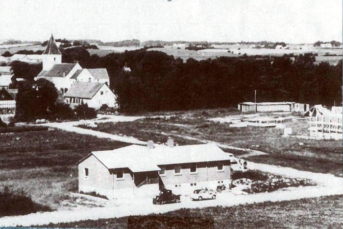 Lundshøjgårdsvej 36-38. Billedet her er fra 1958. Huset blev opført som lærerbolig og taget i brug 1. august 1958. I den venstre del var der lærerbolig og i den højre lærerindebolig. Det fungerede som sådan indtil 1970. Til højre kan man se Malling Skole under opførelse. Den blev indviet og taget i brug i august 1959. I baggrunden ses Lundshøjgård, hvortil al jorden hørte. Stuehuset bruges nu som præstebolig. Vejen hed indtil kommunesammenlægningen i 1970 Lundshøjvej.