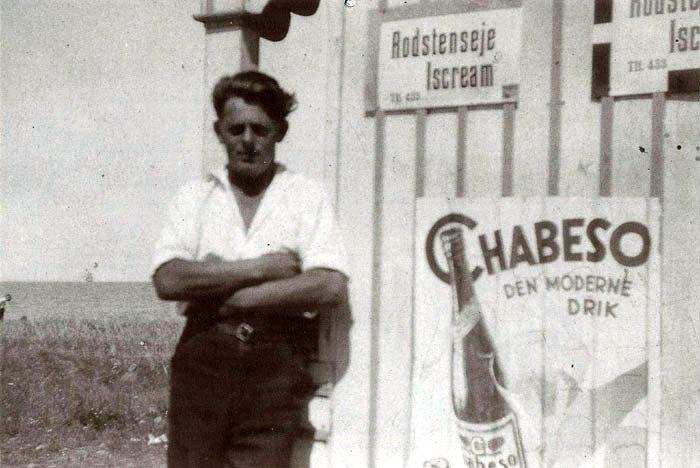 """Niels Sørensen ved ishuset ved Mariendal Strand. Niels Sørensen arbejdede i flere år på Mariendal. Dette billede er fra omkring 1928, da han passede ishuset, der kun var åbent lørdag og søndag. Niels Sørensen boede indtil sin død i oktober 2000 på Kirkebakken i Beder. Bemærk reklamerne på ishuset. Hvad Chabeso er Vides ikke, men isen er fra """"Rodstenseje"""", hvor der altså dengang var et mejeri. Efter sigende var flødeisen derfra virkelig god."""