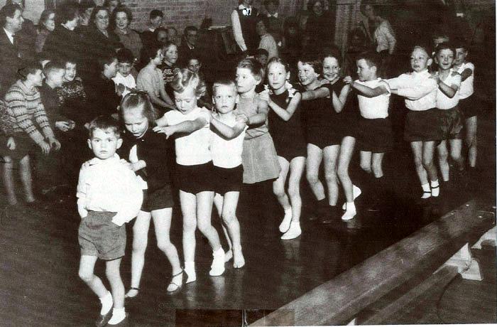 """Beder og Omegns Ungdomskreds afholder gymnastikopvisning d. 18. marts 1963 på Beder Skole, Kirkebakken. Forældre og søskende sidder og står langs væggene, mens de mindste gør sig klar til at vise, hvad de har lært. """"Formanden"""" har ikke en skulder at holde ved, så helt upåvirket af situationens alvor har han stukket hænderne i lommerne. Hvad hedder han og de andre gymnaster? Nummer 3 fra venstre er Birgitte Aagaard Nielsen."""