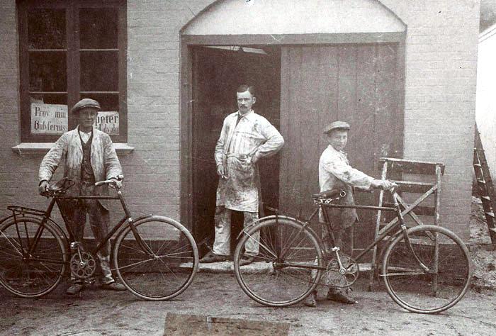 """Beder landevej 55, Beder. Her havde malermester Aksel Truelsen Værksted og beboelse. Manden i døren er snedkermester Niels K. Rasmussen, der boede lige over for. Han var også landpost og havde ruten fra præstegården til Fløjstrup og Mariendal. Han gik under navnet """"Snedker-posten"""". Billedet er fra engang først i 1920-eme. Hvem er de to unge mennesker med de flotte cykler?"""