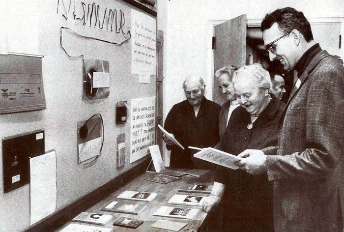 Egnsarkivet udstiller på Malling Skole i 1969. Beder-Malling lokalhistoriske Samling, som det hed, var startet d. 11. nov. 1967, og havde nu så mange arkivalier, at man kunne lave den første udstilling. Formålet var, at give alle indtryk af, hvad et arkiv ønskede at modtage. Det blev også vist, hvordan arkivalierne blev registreret. Samlingen havde til huse i Malling og omegns Bibliotek's lokaler og kunne være i et stålskab med 4 skuffer. Beder-Malling Egnsarkiv har altså her d. 11. nov. 35 års fødselsdag. Se i øvrigt bagsiden af kalenderen. Fra v. står Mary Jensen, Eskesminde, Karen Sørensen, Malling, Tinne Andersen, Malling 0g arkivleder Anders B. Nørgaard, Malling. Bagved ses Johannes Jensen, Eskesminde.