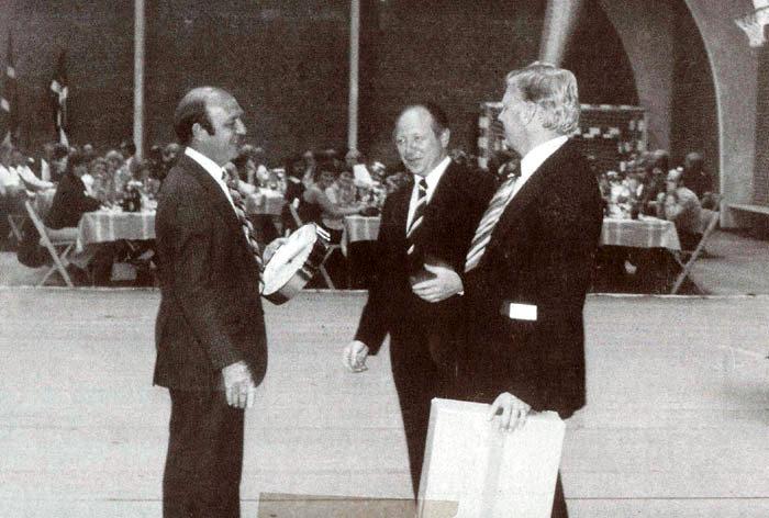 """20-10-1977 blev der, efter en del drøftelser i IF Egelund og Beder Idrætsforening, stiftet en ny forening med navnet """"Beder-Malling Idrætsforening"""", i daglig tale kaldet B.M.I. Formand blev Børge Hougaard og næstformand Kristian Eriksen. Samtidig var byggeriet af den nye idrætshal og svømmehallen godt i gang. Grundstenen blev lagt 31. okt. samme år, og byggeriet stod færdigt i august året efter. På billedet fra indvielsesdagen ses fra v. formand for BMI's hovedafdeling Børge Hougaard, borgmester Thorkild Simonsen og en repræsentant fra byggefirmaet JME, hvis gave var et ur til cafeteriet."""