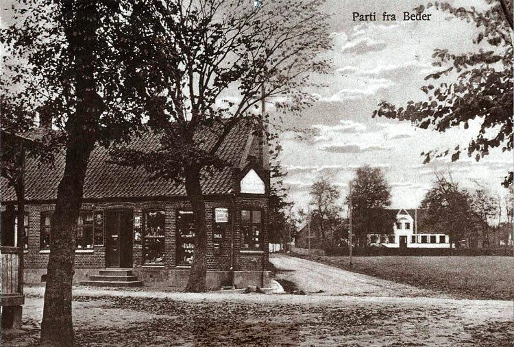 """Et billede fra fordums tid i Beder, ca. 1930. Frands Jensen ejer på det tidspunkt købmandsforretningen på hjørnet. I baggrunden ses """"Kristiansgaard"""" som dengang ejedes af Anton Larsen."""