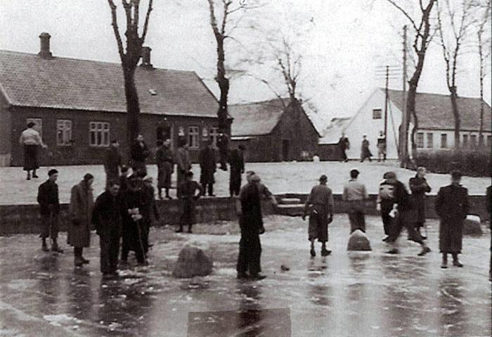 """Vinteren var hård i 1937, og det benyttede eleverne fra Beder Gartnerskole sig af, da bydammen i Beder frøs til. I baggrunden ses """"Damgaard"""", hvis udbygninger blev revet ned først i 1970'erne. I huset til venstre var der i nogle år en tobaksforretning."""