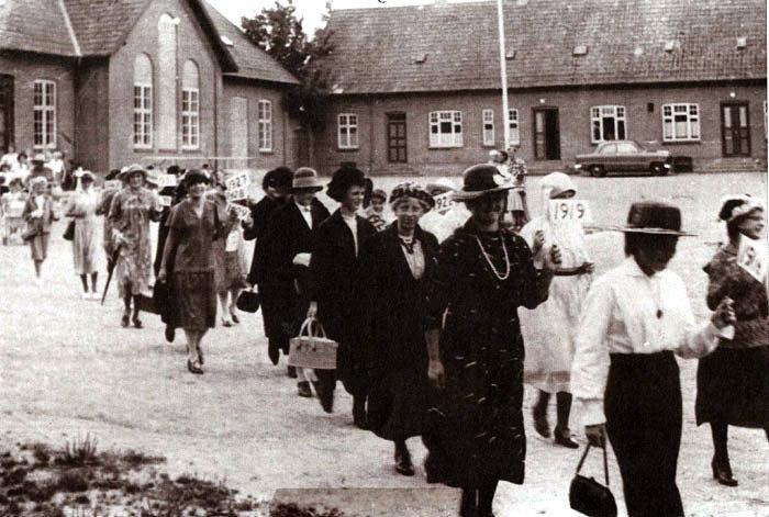 """Optoget ved Malling Gymnastikforenin gs sommerfest starter fra Malling Skole på Tværgade. Pigerne var klædt ud fra hver deres årgang. Det var Ingrid Vedel, der stod for dette arrangement. """"1919"""" er Hanne Andersen og Bodil Hansen (bag Hanne), """"1893"""" er Bodil Frank, """"1890"""" er Kirsten Torstensen, """"1898"""" er Anne Andersen."""