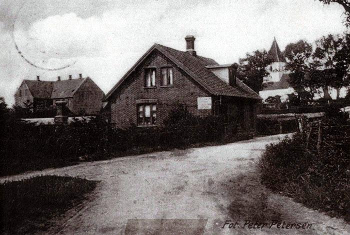 """Malling Kirkevej 12 Huset er formentlig bygget i 1903, bag på huset sidder en mursten med dette årstal. Det blev bygget af murersvend Anders Andersen, der indrettede en """"Tusindhandel"""" i huset, en butik med bla. galanterivarer og handel med træsko, som han også reparerede. Hans kone passede butikken, den efterhånden store bømeflok og havde desuden rulleforretning. Bygningen i baggrunden er den nuværende """"Danske-Bank"""" bygget i 1908."""