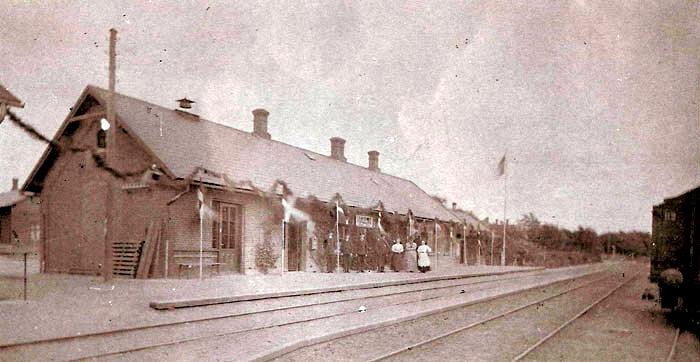 """Personalet på Malling Station er klar til at modtage det første tog fra Hou, 19. juni 1884. Stationen er fint pyntet med guilander. Sangforeningen modtager toget med en sang skrevet til lejligheden: """"Se, hurra, der har vi toget. Herlig kommer dampens hest"""". Købmand Niels Jensen serverer forfriskninger til passagerne, og et par hundreder af byens borgere er mødt op. Toget bliver sendt af sted med endnu en sang: """"Så farvel, af sted!"""". Sangforeningen står endda parat, da toget vender tilbage fra Århus sent om aftenen."""