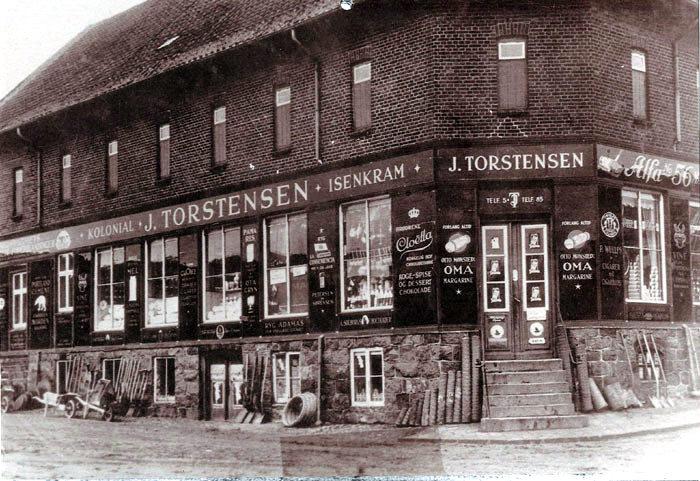 Jens Torstensens købmandsgård i Malling på hjørnet af Ajstrupvej og Stationspladsen ca. 1920. Da jernbanen åbnede i 1884,flyttede købmand Niels Jensen sin købmandshandel fra Norsminde til Malling. Jens Torstensen købte forretningen i 1891. I 1936 brændte bygningen, men blev genopført. Bygningen anvendes fortsat til erhverv.