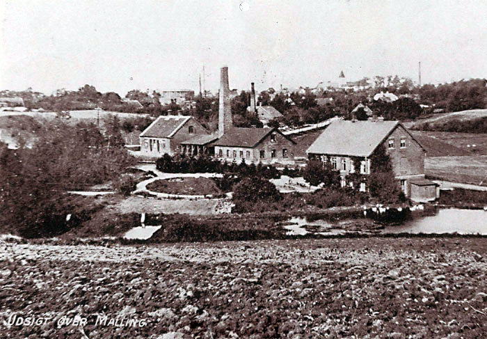 """Bækvej i Malling set fra syd. Mod nord skimter man i baggrunden Malling kirketårn. Huset til venstre på hjørnet af Bredgade og Bækvej kaldes """"Trædrej erens hus"""".  I midten ligger Malling Teglværk med skorstenen og laden til at tørre teglstenene. Teglværket producerede ca. 400.000 sten om året og var i funktion fra 1896 til ca. 1950. Huset yderst til højre kaldes """"Teglbrænderhuset""""."""