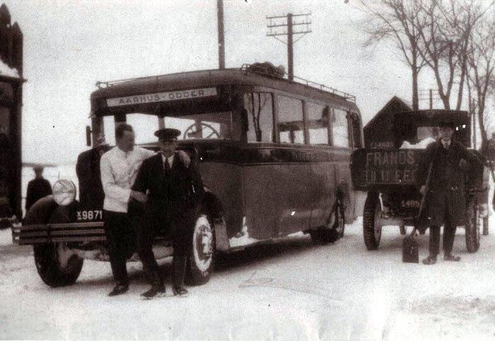 Rutebilen fra Odder til Århus holder ved købmand Frands Jensen i Beder, der hvor Netto nu ligger. Lastbilen er fra ca. 1925. Er der nogen, der kender personerne?