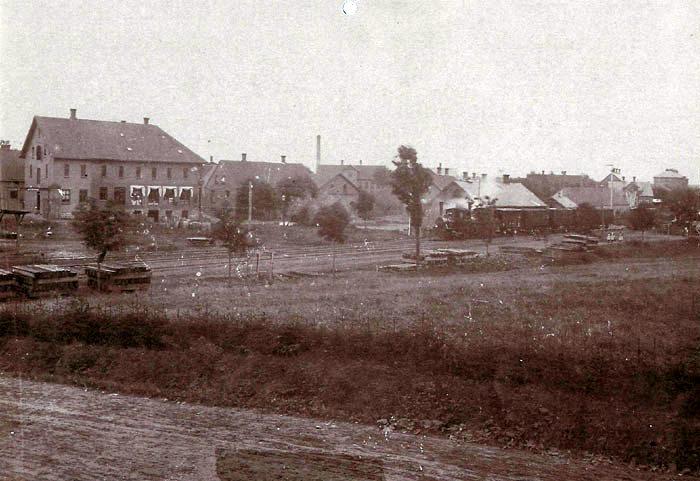 """Udsigt fra Gammel Østergårdsvej til Stationspladsen i Malling ca. 1905. Bygningen til venstre med markiserne er købmand Torstensens forretning, den høje skorsten i baggrunden tilhører Malling Stavfabrik og Savværk. Helt til højre i billedet ses Malling Landbrugsskole. Foran stationen holder en række godsvogne med to lokomotiver foran begge med dampen oppe. Fotograf er Kr. Bach """"specialist i friluftsfotografi"""", som der står på fotorammen. Kr. Bach har taget en de] billeder af Virksomheder og ansatte i Malling."""