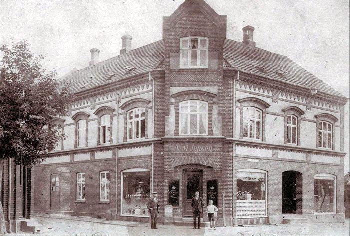 """På hjørnet af Malling Kirkevej og Bredgade lå indtil omkring 1900 """"Stenhøj gård"""". Da den var flyttet til Tværgade, byggede Niels Michael Jensen og hans mor en købmandsforretning. Bemærk den fine teglstensdekoration, den kan ikke længere ses, da bygningen er blevet pudset og i dag står i hvidt. Der har været bank i bygningen siden slutningen af 1960'erne. Personerne på billedet fra 1920'erne er købmand Niels M. Jensen, """"reserveposten"""" Christian Nielsen og Oluf Andersen."""