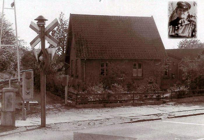 """Billedet er af ledvogterhuset Bredgade 77 i Malling fra perioden 1960-1970. Til venstre på billedet ses blinksignalet og den nu automatiske bom. Det indsatte billede er af """"bommersken"""" eller ledvogteren Johanne Jørgensen fotograferet ved sin afsked fra banen i 1960, da overskæringen blev automatiseret. Det var Johannes opgave at sænke bommene i god tid før toget korn, og efterfølgende få dem hævet igen. I 1884 er der 5 offentlige plus 11 private overkørsler i Beder-Malling kommune. 1966/67 etableres et nyt trinbrætt syd for Malling """"Banevolden"""" ud for et nyt boligkvarter af samme navn."""