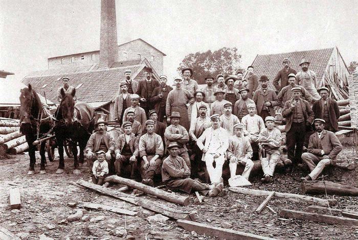 Fotograf Kr. Bach, der betegnede sig selv som specialist i friluftsfotografi, har taget billedet af de ansatte ved Malling Dampbødkeri og Savværk i Bredgade 63. Virksomheden skiftede senere navn til Malling Stavfabrik, hvor der blev udskåret stave til smørdritler. Billedet er fra begyndelsen af 1900-tallet. April