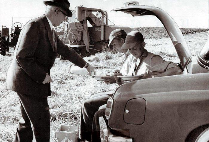 Høsten er i gang, i baggrunden ses mejetærskeren med de endnu tomme kornsække. Forstanderen på Malling Landbrugsskole Søren Larsen-Sørensen giver eleverne en forfriskning under arbejdet. Foto 1958