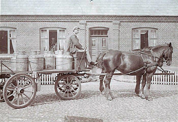 Mælkekusk Johannes Nielsen holder på den stenbelagte  gårdsplads på Elmosevej 40, Neder Fløjstmp by, Malling. Bygningen er opført i 1909. Han er med sin hestevogn med mælkejünger på vej til Beder Mejeri. Landbruget var langt det største erhverv i kommunen. I 1925, hvor billedet er taget, boede der ca. 1805 personer i Beder-Malling Kommune, heraf var ca. 970 beskæftiget med landbrug, ca. 460 i handel/industri.