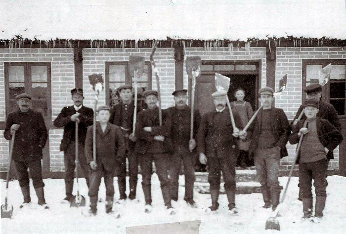 Snekasterne (måske karlene fra de omkringliggende gårde) foran stuehuset til Nielsminde, Malling Bjergevej 119.  Nr. 4 fra venstre er Niels Øvlisen, i døren ses Bolette Øvlisen. Foto 1910-20