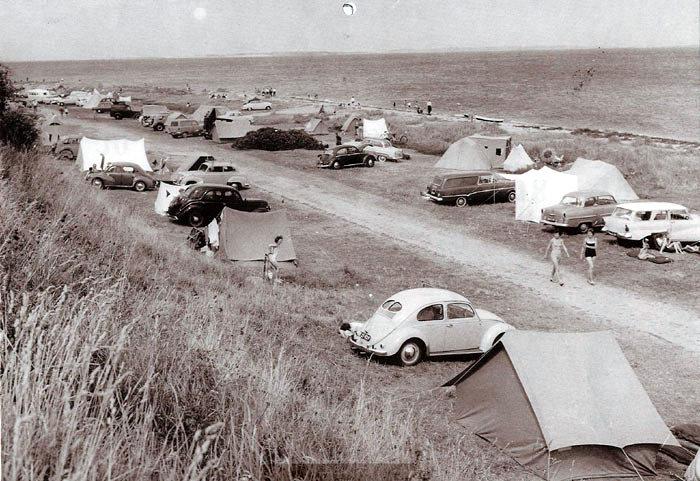 Sommerferien er begyndt, der camperes på Ajstrup Strand. Alle ligger i telt, og mange har bilen med. Opel og Volkswagen dominerer, og de første stationcars er på banen. Nogle enkelte førkrigsmodeller ses dog også. Foto 1962