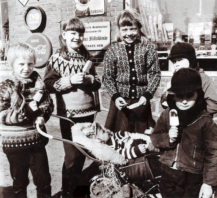 Det er stadig koldt, men forårssolen frister til en ispind. Billedet er taget uden for købmand Dichs forretning på Gammel Østergårdsvej 22, Malling. Desværre kender arkivet ikke børnenes navne. Kan nogen hjælpe? Foto 1965